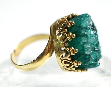 closeup photo of gold-colored ring with green gem
