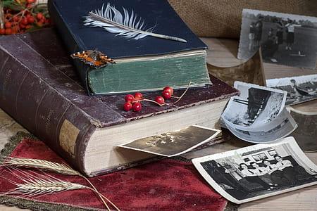 two hardbound books near photographs
