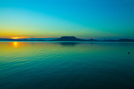 blue body of water and silhouette mountains