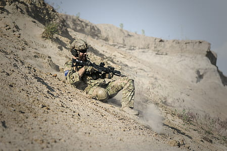 Soldier Man With Black Rifle Sliding on Cliff