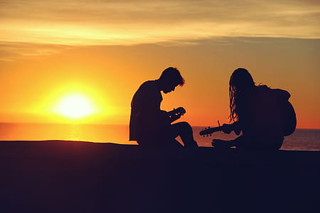 silhouette of two people holding string instruments during sunset