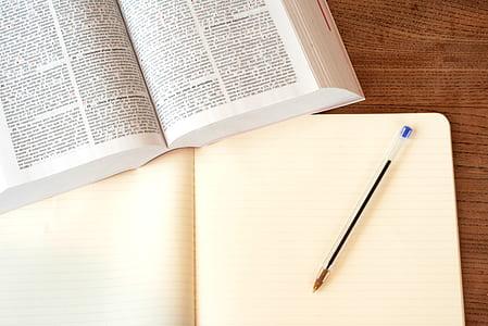 white book beside blue ballpoint pen