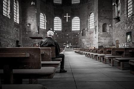 man in black jacket on wooden chair inside church