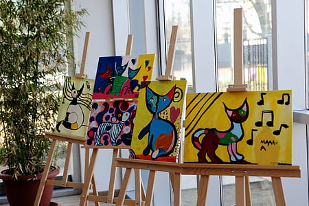 five cat paintings with easels