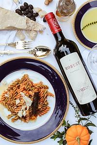 Robust liquor bottle besides spiral pasta on white and black ceramic plate