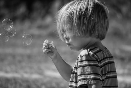 grayscale photograph of toddler blowing bobbles