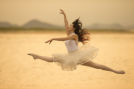 woman in white sleeveless dress doing ballet