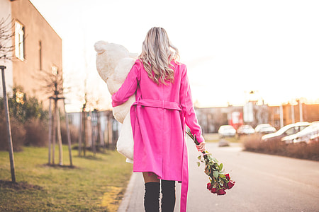 Woman with Big Teddy and Roses Walking on the Street