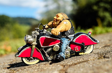 selective focus photo of man in white shirt ride on red and black cruiser motorcycle scale model