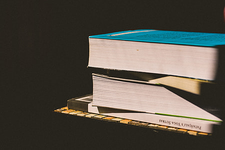 Books stacked up on a black background
