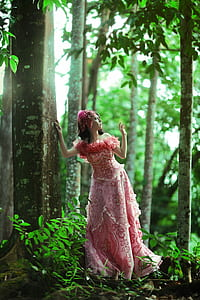 woman wearing pink and red floral off-shoulder dress standing near tree