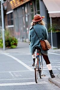 person wearing blue jacket riding bicycle during daytime