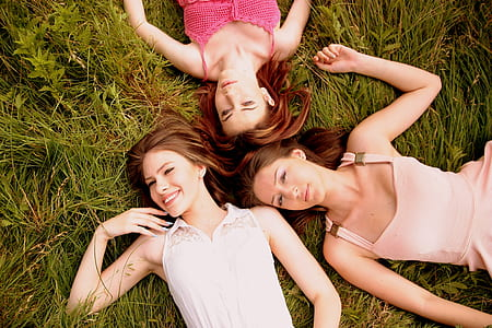 three women laying down on green grass lawn
