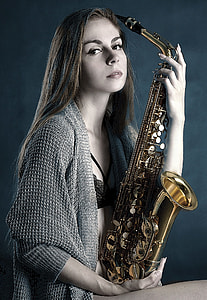 woman holding brass saxophone photography