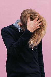blonde hair man wearing black sweater scratching he's head during daytime