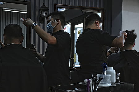 two man in black shirt doing haircut during daytime