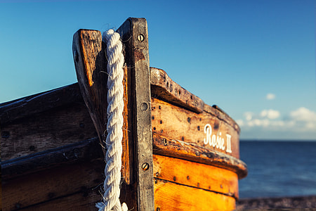 A wooden fishing boat rests on the beach on a sunny day in Deal in Kent, England