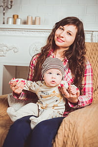 woman in red and brown plaid dress shirt holding baby