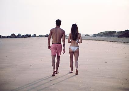 women's white bikini and men's red beach short