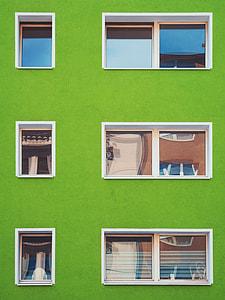 green concrete building with white frame window