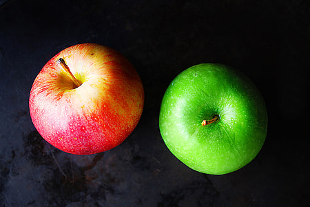 Red and green apples on dark background