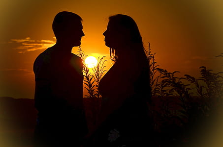 silhouette photo of man and woman standing during golden hour