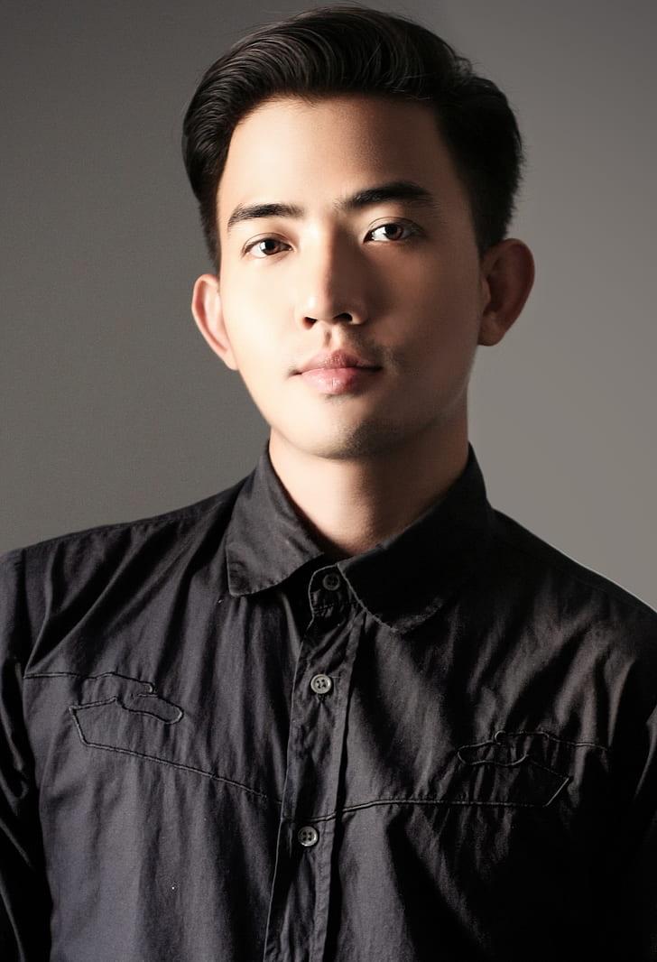 man standing near wall wearing black button-up collared shirt