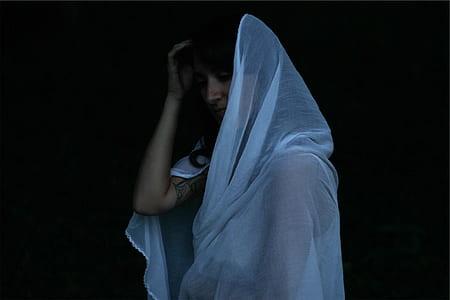 woman wearing white sheer headdress standing in black background
