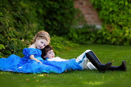 two girl and boy wearing dresses lying down on green grass field