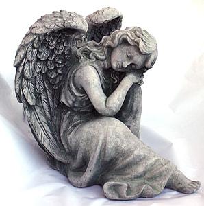gray concrete figure of an angel sleeping