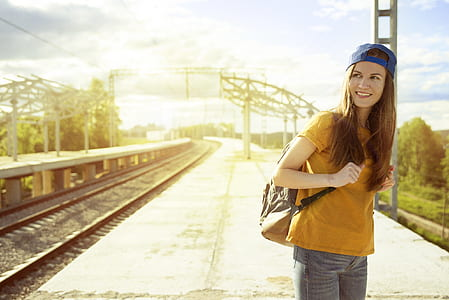 woman wearing yellow crew-neck t-shirt, blue cap, and carrying backpack