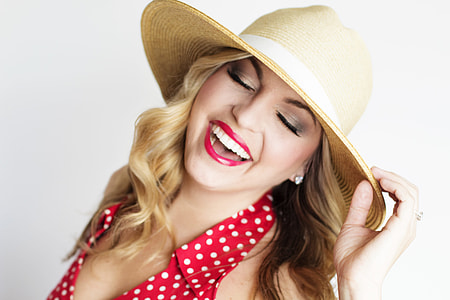 woman in red and white polka-dot blouse smiling white holding brown straw sun hat