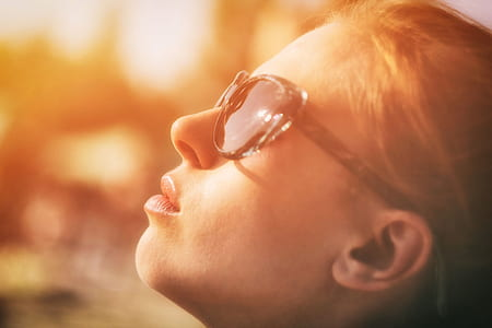 photography of woman wearing sunglasses looking towards sky