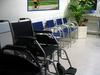 black and gray wheelchair beside blue chair with gray steel frame