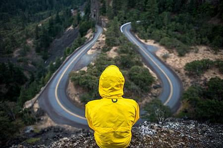 person wearing yellow coat sitting on mountain edge
