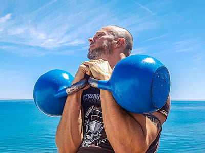 Man Lifting Pair of Blue Kettlebells
