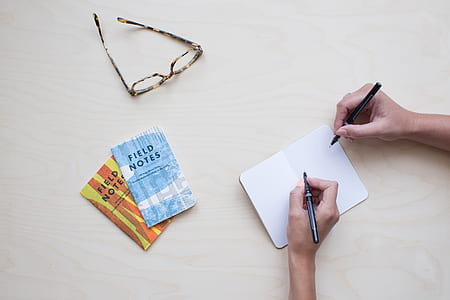flat lay photography of two persons writing notes