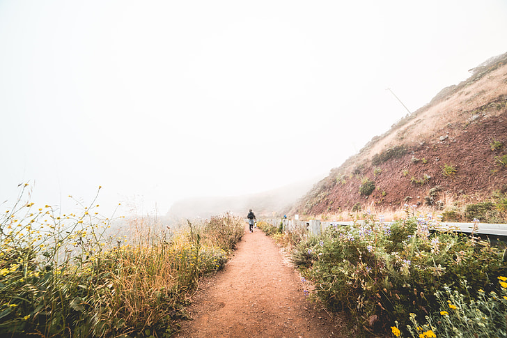 Young Woman Hiking the Mountain Trail in Foggy Weather