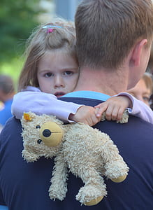man carrying girl holding bear teddy bear
