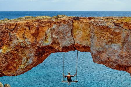man swinging under cliff