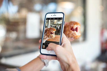 person taking photo of a pie