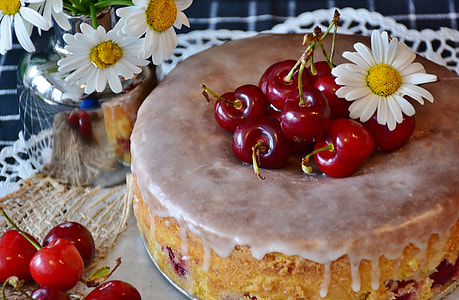 round baked cake with cherries