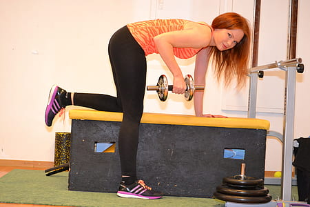 woman in orange tank top and black yoga pants holding silver dumbbell