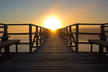 photo of brown wooden bench near ocean during sunrise