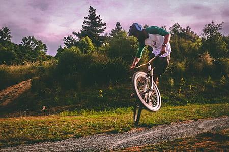 Man in White and Green Raglan Elbow-sleeved Shirt Biking at Daytime