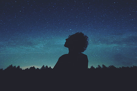 silhouette of person wearing glasses looking at the sky during nighttime