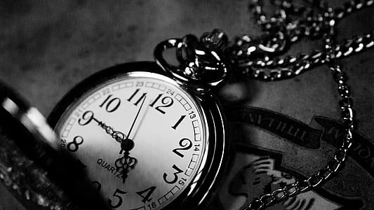 grayscale photo of silver-colored pocketwatch