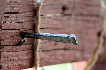 close up photo of gray nail on wall
