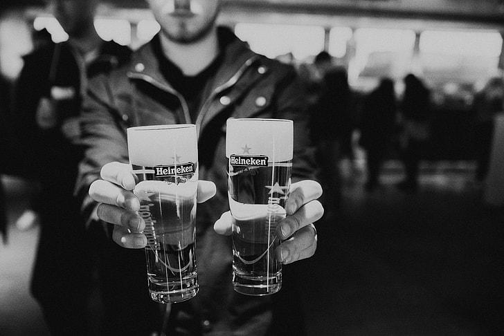 man holding two Heineken beer glasses