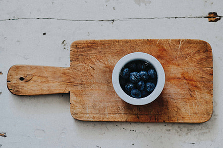 photo of white ceramic cup on brown wooden chopping board